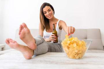 A young beautiful Woman relaxing on a sofa with Beer and potato