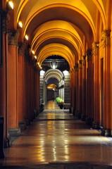 Arkadengang mit Säulen und Spiegelung der nächtlichen Beleuchtung auf dem Boden