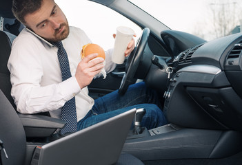 Man eating fattening food and working seated in car