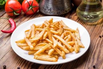 Tasty french fries on cutting board,  wooden table