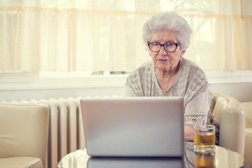 Concentrated senior woman using laptop at home.