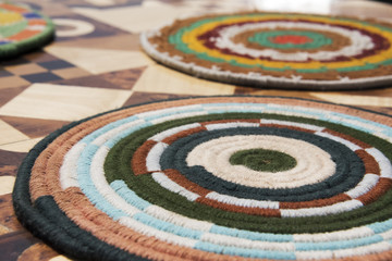 Brightly coloured woven placemats on a marquertry table top