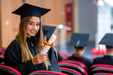 education, graduation, and people concept - group of happy international students in mortar boards and bachelor gowns with diplomas