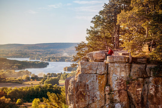 Man sitting on rock outcrop at Gibraltar Rock, Wisconsin.