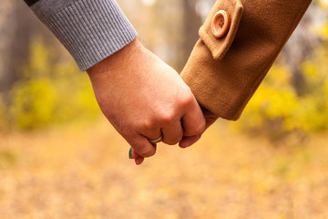 Closeup view of couple hands holding. Man and woman walking outdoor in autumn park. Love and romantic lesure activity