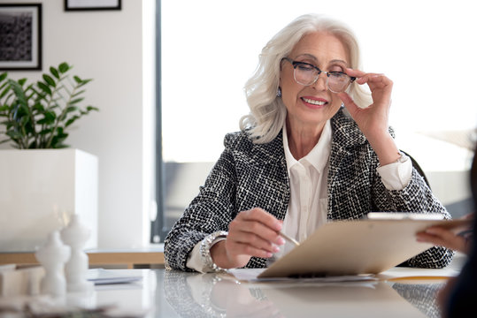 Positive old business woman is signing papers