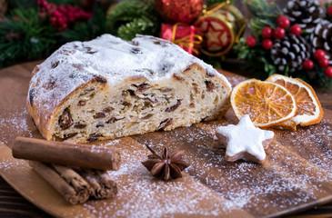Weihnachtlicher Butterstollen mit Rosinen auf Holztisch mit Gewürzen und Puderzucker