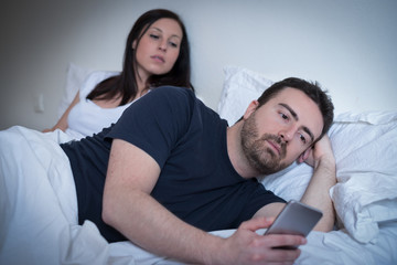 Man neglecting his girlfriend and using his mobile phone in bed