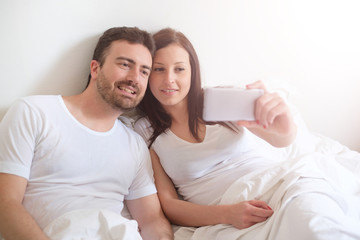 Happy couple taking a selfie with mobile phone