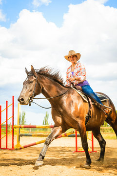 Cowgirl in western hat doing horse jumping