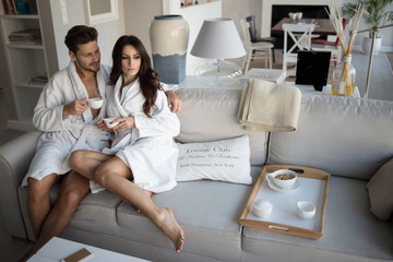 Loving couple drinking coffee in the morning while sitting on the couch