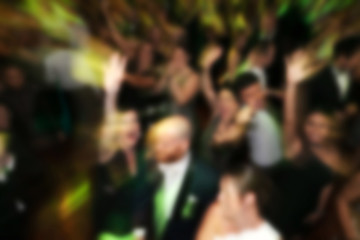 blurry background of men and women dance in nightclub