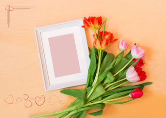 Picture frame and tulip flowers on wooden background