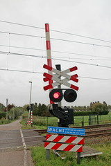 Railroad crossway with red light where number of Saint Andrew's crosses marks the number of tracks