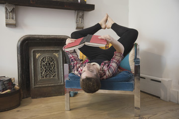 Man reading book while lying upside down on armchair