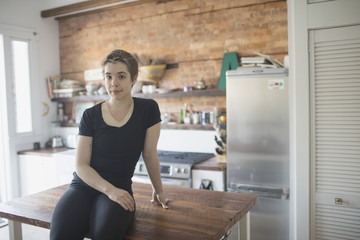 Transgender person sitting on their kitchen counter