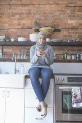 Muslim woman wearing a hijab using her smart phone