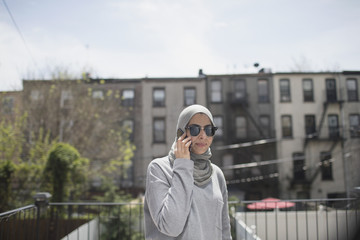 Muslim woman wearing a hijab and sunglasses taking a phone call