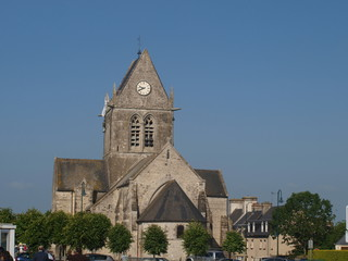 Famous church of Sainte-Mère-Église with dummy paratrooper on it.