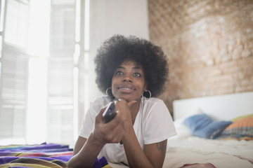 Woman watching television on her bed