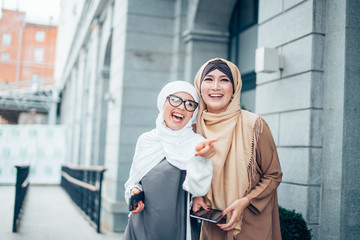 two muslim girls laughing and pointing fingers