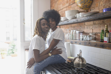 Lesbian couple embracing in their kitchen