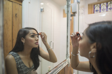 Young woman applying makeup in her bathroom mirror