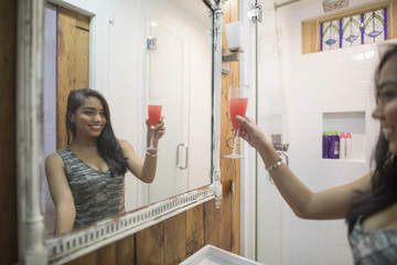 Young woman holding a cocktail in her bathroom mirror