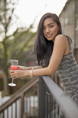 Young woman with a cocktail on her balcony