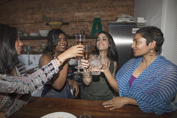 Smiling friends toasting beer glasses during party
