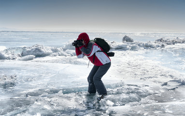 the photographer takes pictures on the ice of lake Baikal