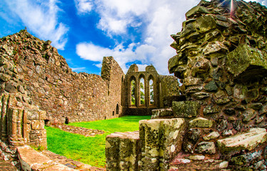 Riuns Landscape of Inch Abbey with a blue sky in Northern Ireland. Monastery ruins in Downpatrick. Co. Down. Travel by car in summer.