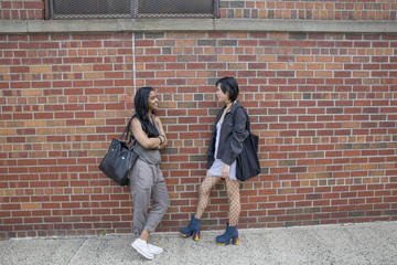 Young women talking beside a brick wall