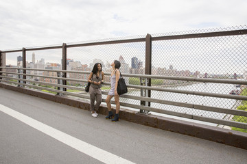 Friends talking on a bridge in Queens
