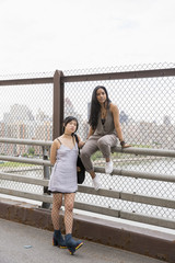 Young women posing on a bridge