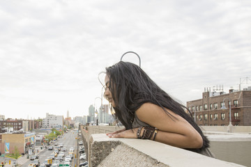Young woman leaning on a bridge in Queens, New York