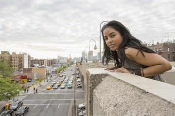 Portrait of young woman leaning on a bridge in Queens