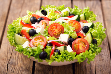 bowl of fresh salad on a wooden table