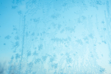 Beautiful abstract snowflake Christmas background. Ice texture on the window. Frozen snowflakes and frost. Christmas winter background. Colored in blue tone