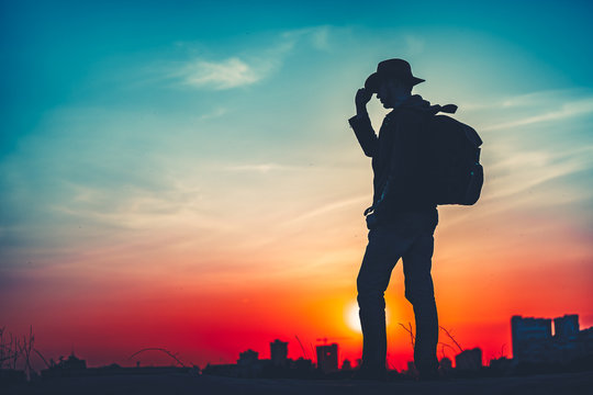 Travel Concept. Silhouette of a man with a backpack against bright sky sunset. Sun goes down. A man looks ahead, straightens his cowboy hat. Cityscape night view in the background. Color toning filter