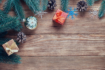 Christmas background. Branches of a Christmas tree, ball and gift boxes on a wooden background with copy space.
