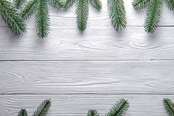 Christmas background. Branches of a Christmas tree on a wooden background with copy space.