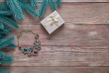 Christmas background. Branches of a Christmas tree, women's necklace and gift boxes on a wooden background with copy space.