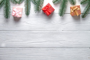 Christmas background. Branches of a Christmas tree and gift boxes on a wooden background with copy space.