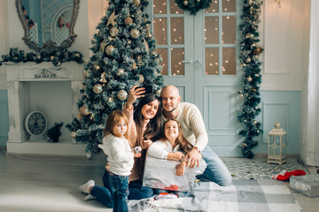 miling young family in Christmas atmosphere making photo with smartphone