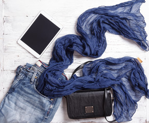 Set of woman's items including scarf, tablet, handbag and jeans.