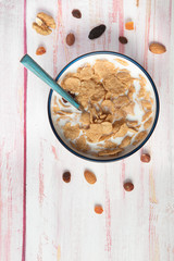Bowl of cornflakes and milk, hazelnut, dry apricot, walnut and nuts on wooden background , top view,  close-up