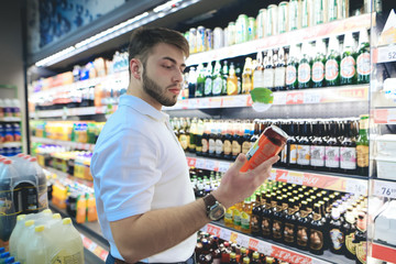A handsome bearded man chooses beer in a supermarket. The buyer buys alcohol at a supermarket. A man looks at a can of beer