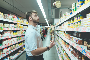 A beautiful man chooses canned food from supermarket shelves. A man with a beard juggles the goods in the store.
