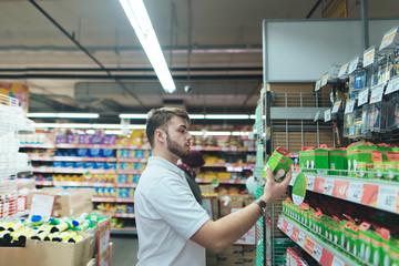A man chooses goods for a house in a supermarket. Shopping in the store.